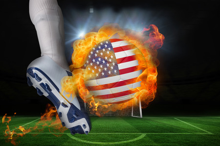 Football player kicking flaming usa flag ball against football pitch and goal under spotlights photo