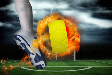 Football player kicking flaming belgium flag ball against football pitch under stormy sky photo
