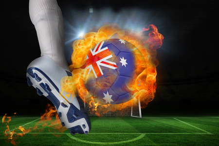 Football player kicking flaming australia flag ball against football pitch and goal under spotlights photo