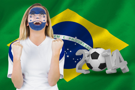Excited honduras fan in face paint cheering against world cup 2014 with brasil flag photo