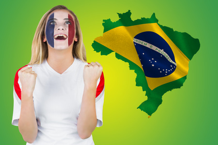 Excited france fan in face paint cheering against green brazil outline with flag photo