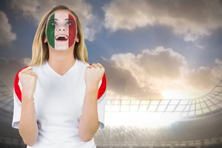 Excited italy fan in face paint cheering against large football stadium under cloudy blue sky photo