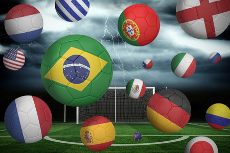 Footballs in various flag colours  against football pitch under stormy sky photo