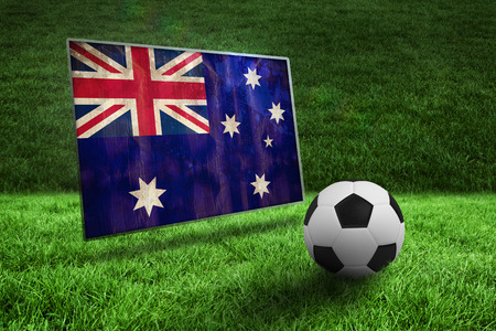 Black and white football on grass against australia flag in grunge effect photo
