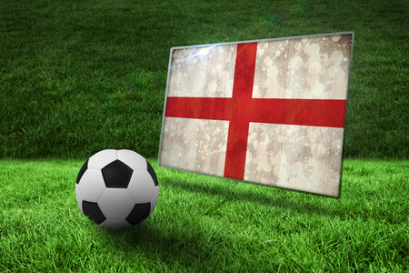 Black and white football on grass against england flag in grunge effect photo