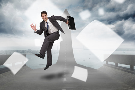 Smiling businessman in a hurry against road turning into arrow photo
