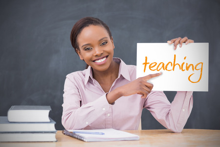 Happy teacher holding page showing teaching in her classroom at school photo