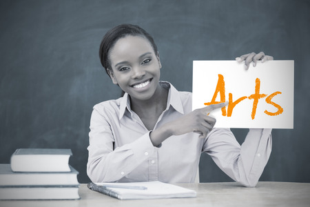 Happy teacher holding page showing arts in her classroom at school photo