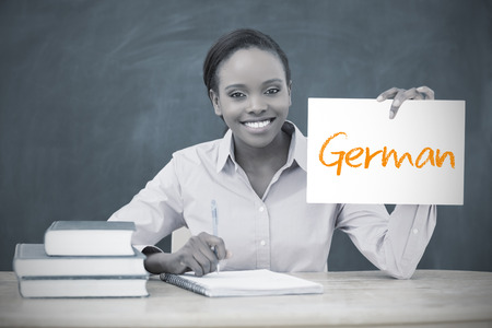 Happy teacher holding page showing german in her classroom at school photo