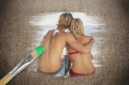 Composite image of couple on the beach with paintbrush dipped in green against weathered surface  photo