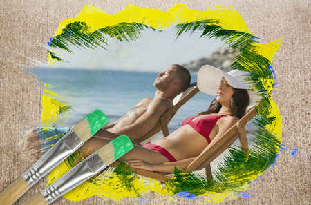 Composite image of couple lying on the beach with paintbrushes dipped in green against weathered surface  photo