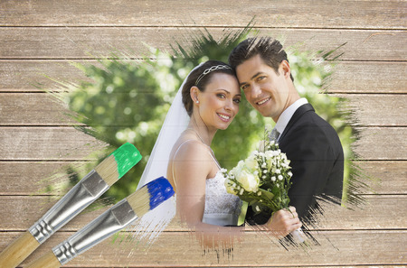 Composite image of newlyweds smiling at camera with paintbrush dipped in blue against wooden surface with planks photo