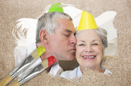 Composite image of senior couple celebrating birthday with paintbrush dipped in red against weathered surface  photo