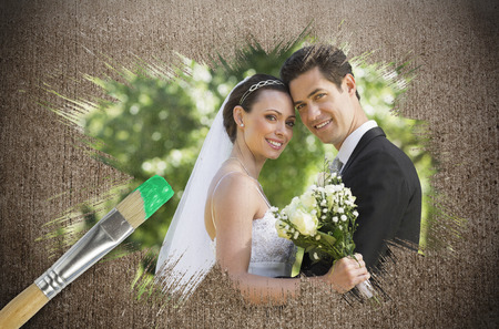 Composite image of newlyweds smiling at camera with paintbrush dipped in green against weathered surface  photo