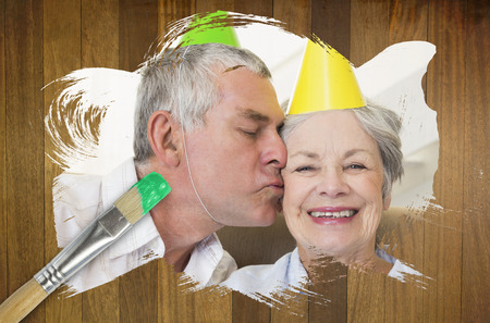 Composite image of senior couple celebrating birthday with paintbrush dipped in green against wooden surface with planks photo