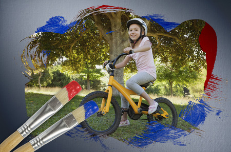 Composite image of little girl on a bike with paintbrush dipped in blue against digitally generated grey vignette background photo