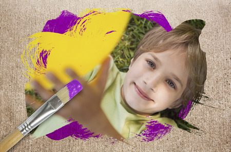 Composite image of little boy smiling at camera with paintbrush dipped in purple paint against weathered surface  photo