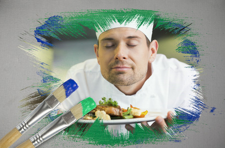 Composite image of chef smelling his dish with paintbrush dipped in green against digitally generated grey background photo