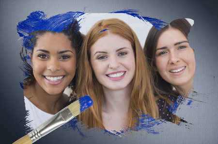 Composite image of pretty friends smiling at camera with paintbrush dipped in blue against digitally generated grey vignette background photo