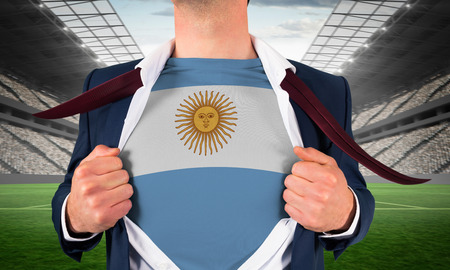 Businessman opening shirt to reveal argentina flag against vast football stadium with fans in white photo
