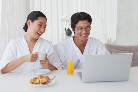 Happy couple using laptop over breakfast at home in the living room photo