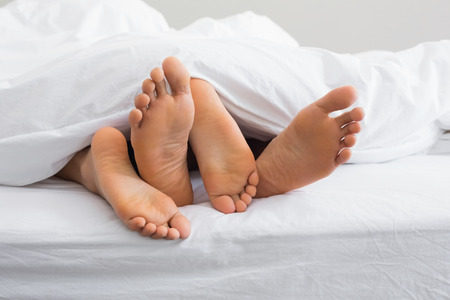 man feet: Couples feet sticking out from under duvet at home in bedroom Stock Photo