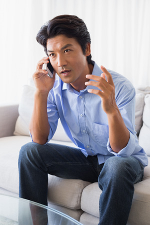 Annoyed man sitting on couch talking on phone at home in the living room Stock Photo