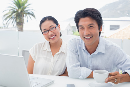 Smiling couple having breakfast together using laptop outside on a balcony photo