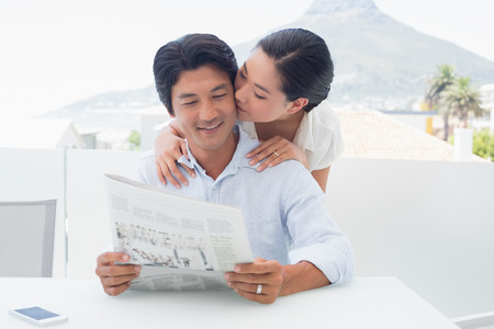 Couple reading a newspaper together outside on a balcony Stock Photo
