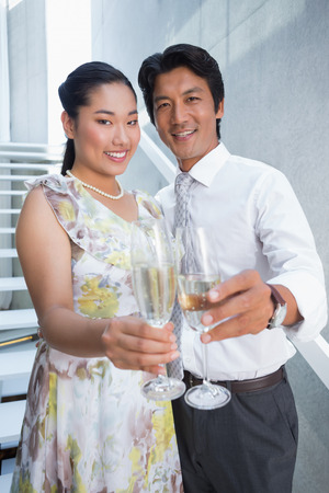 Happy couple dressed up for a date having champagne on the stairs photo