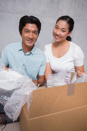 Happy couple sitting on floor unpacking boxes in their new home