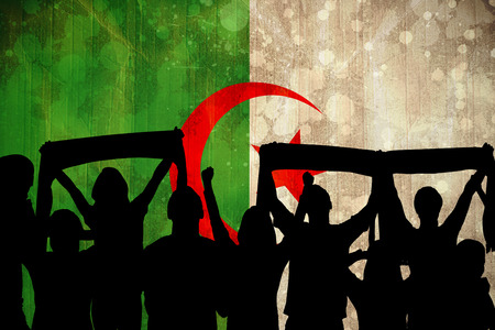Silhouettes of football supporters against algeria flag in grunge effect photo