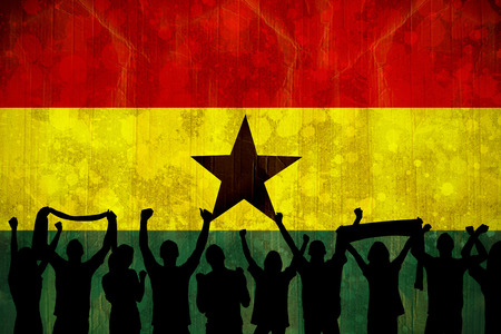 Silhouettes of football supporters against ghana flag in grunge effect photo