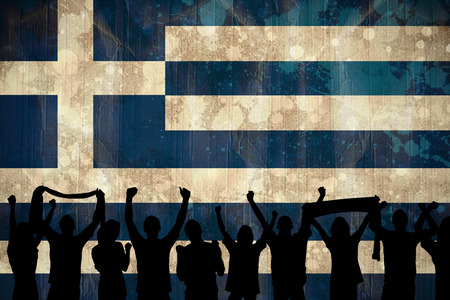 Silhouettes of football supporters against greece flag in grunge effect photo