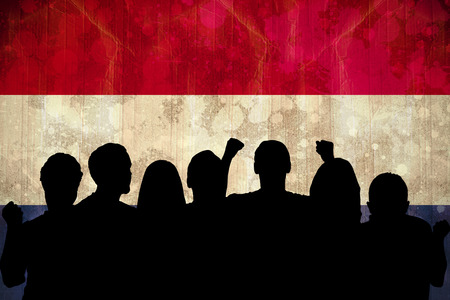 Silhouettes of football supporters against netherlands flag in grunge effect photo
