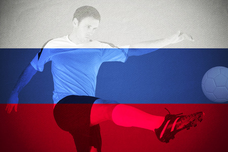 Football player in red kicking against russia national flag photo