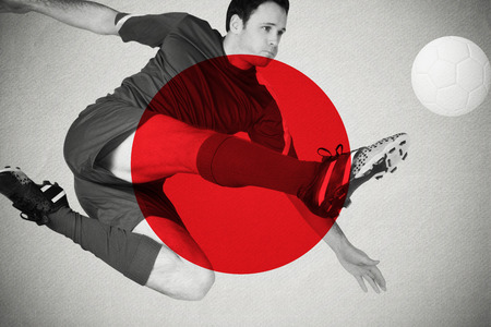 Football player in blue kicking against japan national flag photo