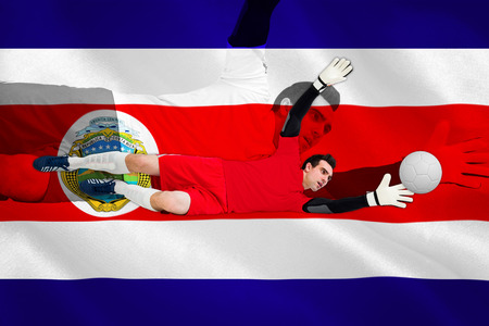 Goalkeeper in red making a save against costa rica national flag photo