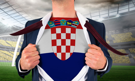 Businessman opening shirt to reveal croatia flag against large football stadium with lights photo