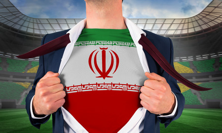 Businessman opening shirt to reveal iran flag against large football stadium with brasilian fans photo