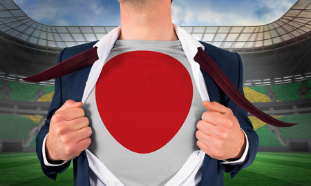 Businessman opening shirt to reveal japan flag against large football stadium with brasilian fans photo