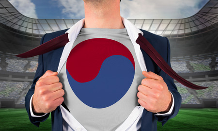 Businessman opening shirt to reveal korea republic flag against large football stadium under spotlights photo