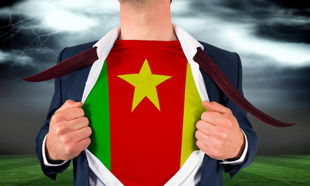Businessman opening shirt to reveal cameroon flag against football pitch under stormy sky photo