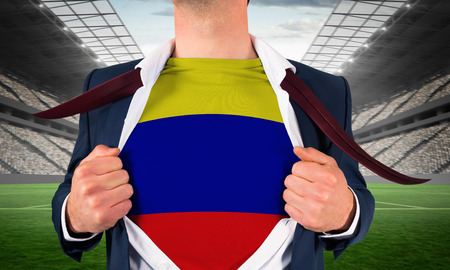 Businessman opening shirt to reveal colombia flag against vast football stadium with fans in white
