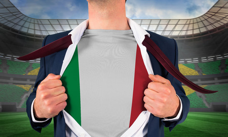 Businessman opening shirt to reveal italy flag against large football stadium with brasilian fans photo