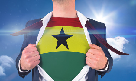 Businessman opening shirt to reveal ghana flag against bright blue sky with clouds photo
