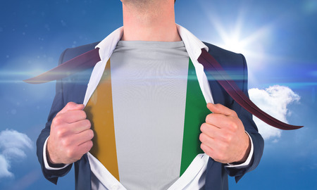 Businessman opening shirt to reveal ivory coast flag against bright blue sky with clouds photo