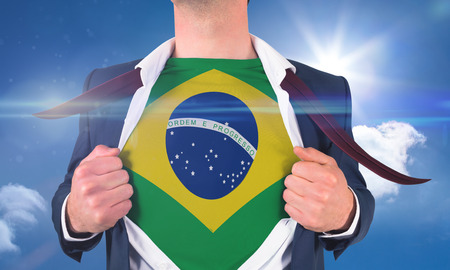 Businessman opening shirt to reveal brasil flag against bright blue sky with clouds photo