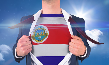 Businessman opening shirt to reveal costa rica flag against bright blue sky with clouds photo
