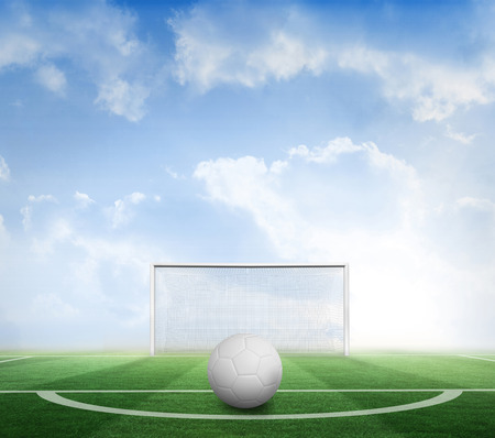 goalpost: Digitally generated white leather football  against football pitch under blue sky